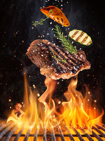 Photo for Tasty beef steaks flying above cast iron grate with fire flames. - Royalty Free Image