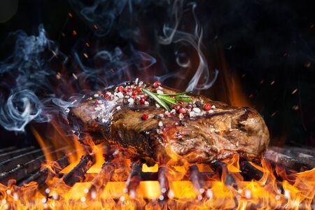 Photo pour Tasty beef steak on cast iron grate with fire flames. - image libre de droit