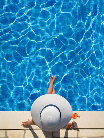 Photo pour beautiful woman in a hat sitting on the edge of the swimming pool - image libre de droit