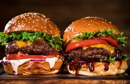 Photo pour Tasty burgers on wooden table. - image libre de droit