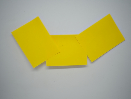Three yellow sticky notes lied on each other on the white isolated background