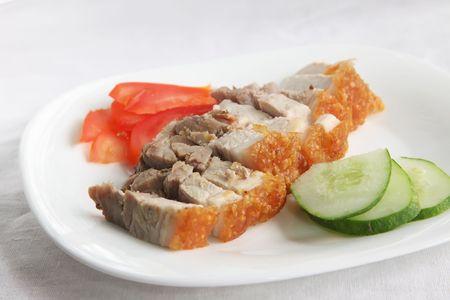Chinese roast pork with crispy skin, sliced on plate