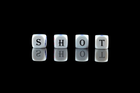 Group of White dice over black background with word written SHOT