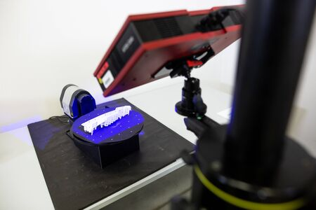 Professional 3D scanner scanning an industrial object, plastic molding placed on a turntable, metrology concept