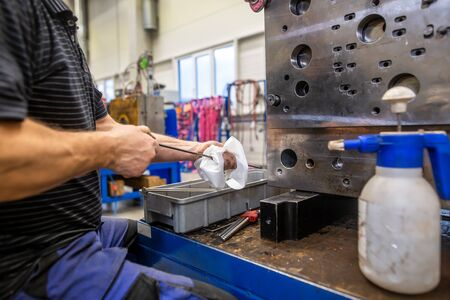 Photo pour Engineer doing maintenance on the injection mold after production, cleaning injection mold - image libre de droit