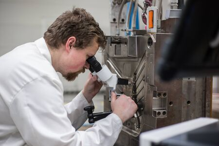 Photo pour quality engineer checks deficiencies on the injection mold by a microscope - image libre de droit
