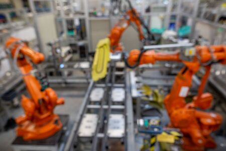 View to three automatic robots arm machine in automotive industrial, smart factory, blur image for background