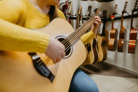 Photo pour Young woman trying, buying new guitar in a instrument shop, instrumental concept - image libre de droit