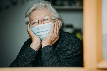 Foto per Senior woman with medical mask at the home during coronavirus, covid-2019 pandemic, stay home - Immagine Royalty Free
