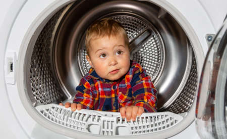 Photo pour Close up of portrait lovely kid looks out from the washing machine, funny concept - image libre de droit
