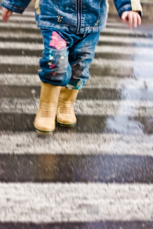Photo for A child runs across the road at a pedestrian crossing. - Royalty Free Image