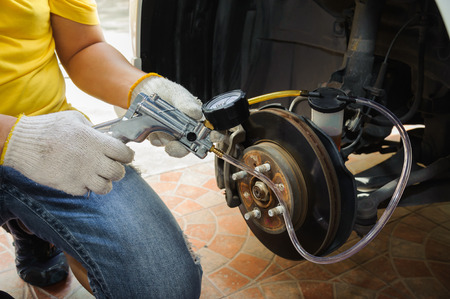Car mechanic bleed air out of brake system