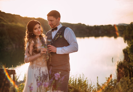 Retro wedding under the open sky.Beautiful bride and happy groom on the background of beautiful nature. The lake.Lavender.Stylish makeup.Loving, sensual young couple.Fashionable toning.