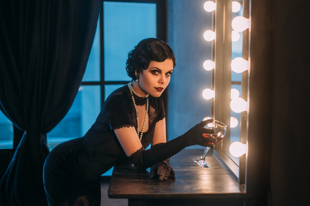 Beautiful Flapper girl with wineglass. Old photo in a retro style. Smokey eyes, hairstyle cold wave. Creative colors