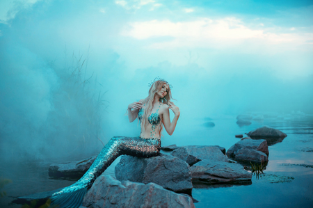 Photo for wonderful young mermaid is relaxing, warming herself in the evening sun - Royalty Free Image
