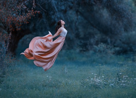 Foto de A young woman, a mysterious witch is floating in the air like a butterfly. - Imagen libre de derechos