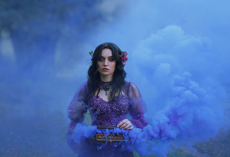 Foto de Pandoras box The treacherous brunette girl in a luxurious dress holds an open casket in her hands and stares intently into the camera with blue eyes. cool smoke in beautiful clouds fills the background. Art photo - Imagen libre de derechos