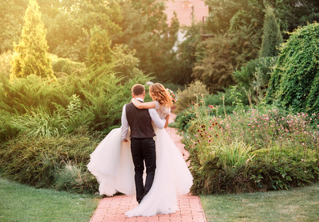 Foto de young groom in a suit carries in arms his bride, wearing a long magnificent luxurious white dress, walking at amazing garden. no faces. picture taken from the back. beautiful romantic photo - Imagen libre de derechos