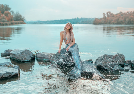Photo for fair-haired mermaid in love dreams of handsome prince, new story Ariel, image of fairy-tale siren with long fish tail, chic crown of shells, plays, sprinkles clear water, ecology of environment - Royalty Free Image