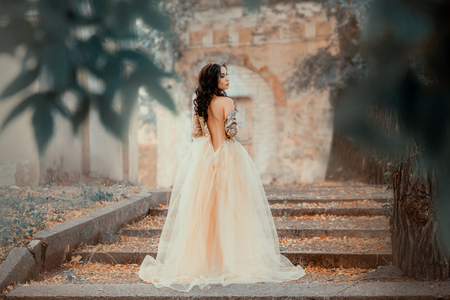 Foto de a mysterious dark-haired girl stands alone in a long elegant gold dress with an open back and a naked shoulder, the magnificent Cinderella escapes from the ball, a proud look, cool colors - Imagen libre de derechos