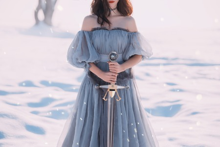 Photo for warlike woman with dark hair in long gray vintage light dress and sharp silver sword in hands - Royalty Free Image