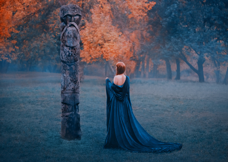 Girl in long blue s dress with bare shoulders walks in misty forest. Woman appeals to otherworldly, supernatural dark forces. sorceress with fiery red hair. Photo from the back, no face in art photo