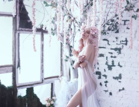 Photo pour Wonderful creation, the girl is a unicorn in light, white, slightly transparent attire. The background is a bright room that is overgrown with plants, moss, ivy, trees and flowers. Art Photo. - image libre de droit
