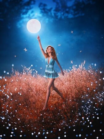 Photo pour pretty leggy beauty with flying flowing hair runs through field of fallen stars behind mystical floating moon. Amazing art photo with creative colors. girl in image of night fairy in short blue dress - image libre de droit