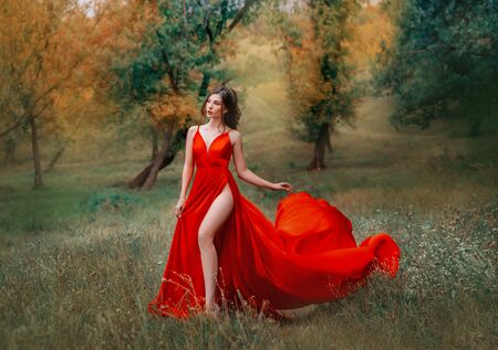 Photo pour Glamorous brunette woman in red scarlett dress very high sexy slit on her leg. - image libre de droit