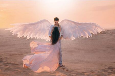 Photo pour Men angel hugs young woman. Long dark hair dress silk fabric flying flutter wind. costume huge white wings. Bright color peach pink yellow sunset desert. Shoot back rear view turned away without face - image libre de droit