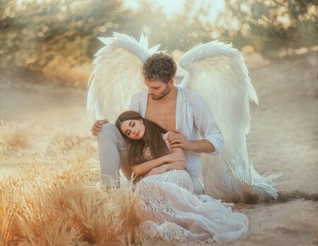 Photo pour Men guardian angel protects and hugs young woman. Sleeping beauty vintage pastel color, miracle dream. Fabulous old warm yellow autumn nature. Bright sun shine light. Creative white suit design wing - image libre de droit