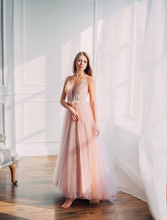Photo pour Beautiful young woman. Blonde long flowing hair. elegant airy peach beige ball gown. evening long pink trendy tulle dress. backdrop white window vintage classic room. Prom holiday image. Stylish look - image libre de droit