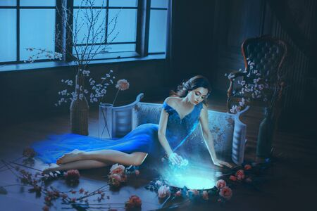 Photo pour Fantasy young sorceress woman in long blue dress touch divine old mirror. Predictor future fairy tale Snow White. magic power of wind light spell. Mystic gothic art photo in dark black medieval room - image libre de droit