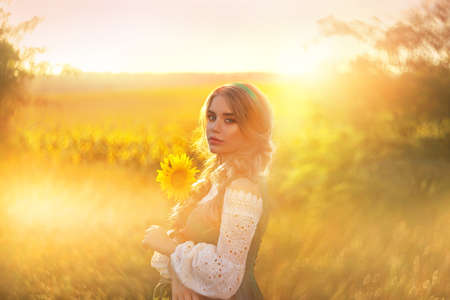 Photo pour Artwork. Portrait young beautiful charming woman, national costume. Green sundress, white sexy blouse. Blonde girl holding yellow sunflower in hands. Blurred backdrop bright summer nature sunny sunset - image libre de droit