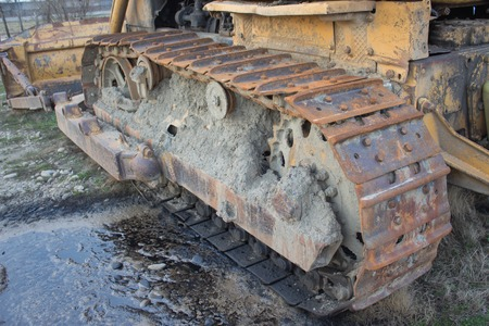 Continuous caterpillar tracks of the bulldozer. Old abandoned, yellow bulldozer. Old rusty and weathered bulldozers