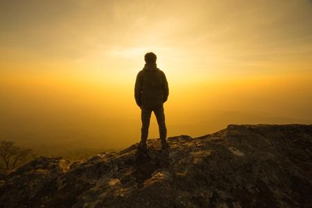 Photo pour silhouette man standing into sunset sky - image libre de droit