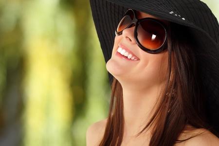 summer teen girl cheerful in panama and  sunglasses enjoying over nature background