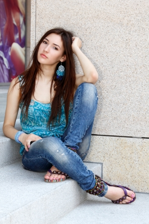 Outdoors portrait of beautiful young sad teen girl sitting on stairs