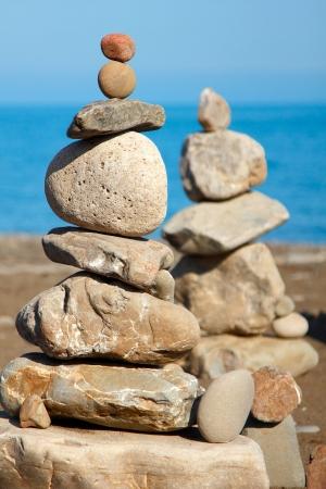 balanced stones pebbles stacks against blue sea