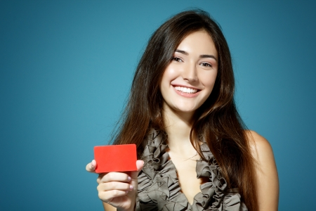 beautiful friendly smiling confident girl showing red card in hand, over blue backgroundの写真素材