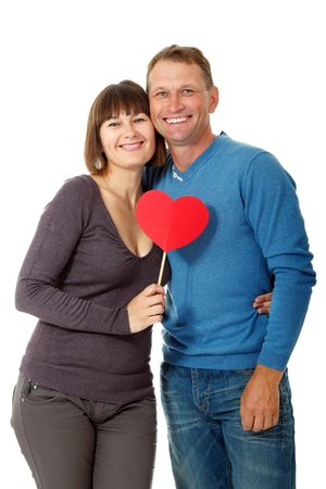 Attractive cheerful woman with man in love smiling over white background. Portrait of happy mature wife hugs her husband with red heart, isolated