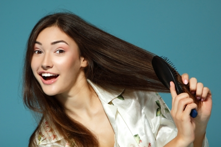 Funny teen girl bombs her hair in the morning. Over blue background.