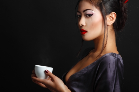 Young beautiful asian woman and tea ceremony, studio shot over black backround with copyspace