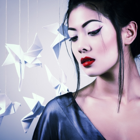 Young beautiful asian woman with origami paper pigeons, studio shot