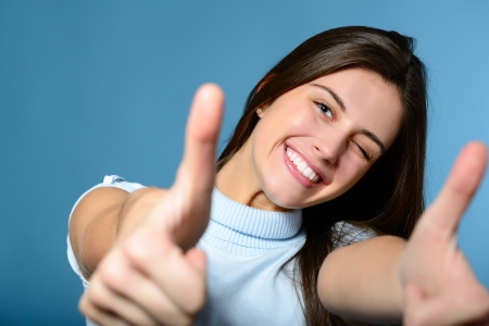 Photo pour Portrait of a beautiful, confident and cheerful teenager girl showing thumbs up isolated on blue - image libre de droit