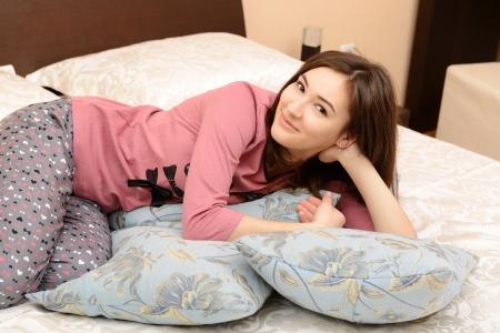 attractive cheerful teen girl in pajamas lying in her bedroom