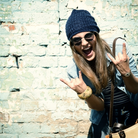 Photo pour portrait of beautiful cool girl gesturing in hat and sunglasses over grunge wall - image libre de droit