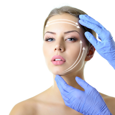 facelift, beauty treatment of the young beautiful female face, doctor's hand in gloves touch face of beautiful young woman isolated on white