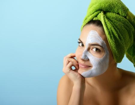 Photo pour Beautiful young woman with facial mask, beauty treatment over blue - image libre de droit