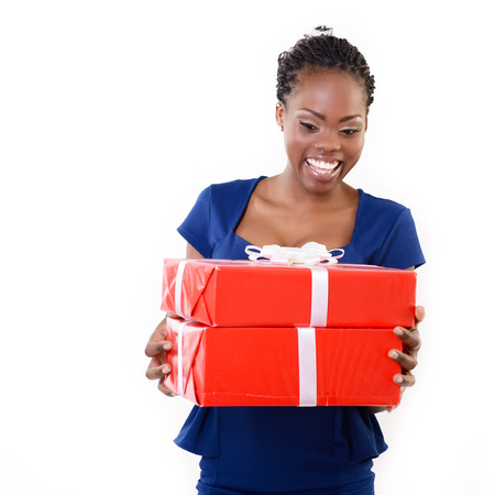 Joyful happy smiling young african woman holding red gift boxes, over white